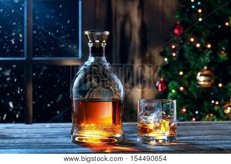 close up view  of glass  with whiskey and bottle  on color back