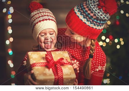 Happy family mother and child girl near a Christmas tree with Christmas present
