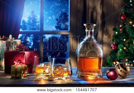 close up view  of two glasses with whiskey and gift boxes on color back