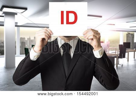 businessman in black suit hiding face behind sign id