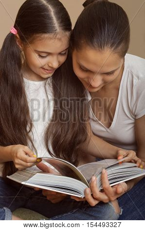 mother explains to the daughter a lesson sit in jeans and white undershirts on a floor