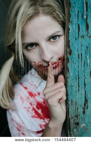 Crazy blonde woman covered with blood making silence gesture. Halloween concept.
