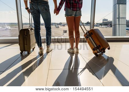 Close up of male and female legs standing in airport near window. Loving couple is holding hands and carrying luggage