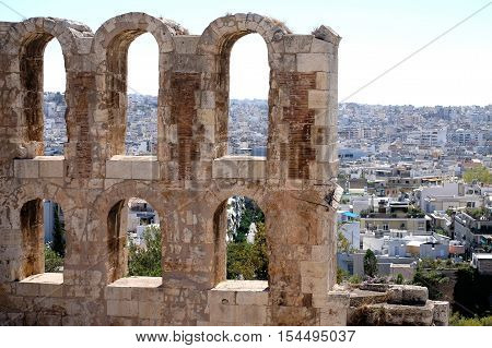a view of ancient stone arches and the city of Athens Greece