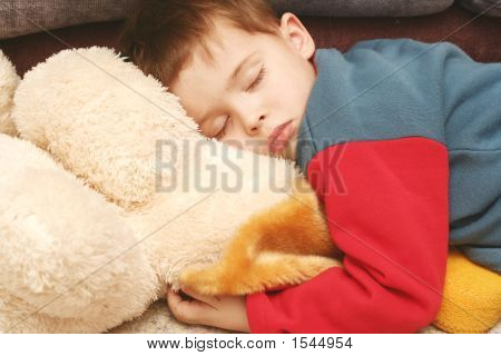 The Child Sleeping In Clothes On A Soft Toy