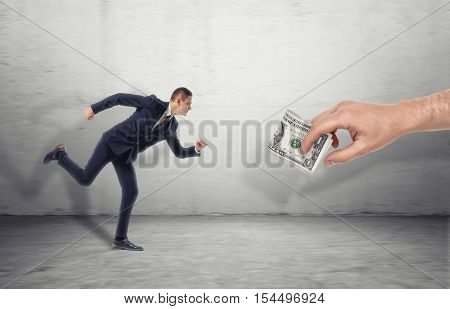 Businessman running for a big man's hand luring with dollar bill on a concrete background. Being motivated by money. Earning much more money. Pursuit of money.