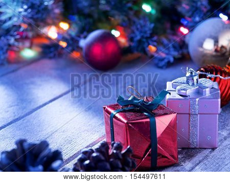 close up view  of lights and gift box on snowbound  wooden back