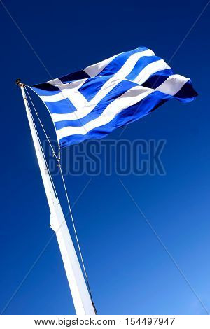 seen from below the greek flag on a flagpole flying in the wind
