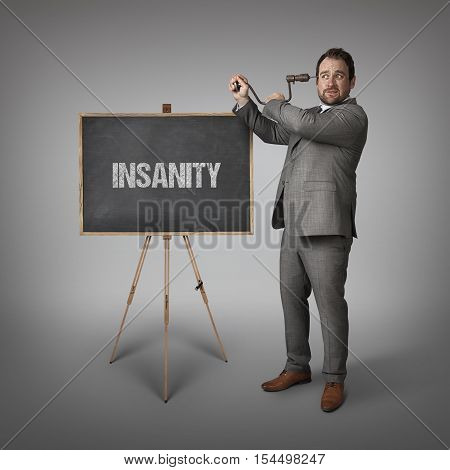 Insanity text on blackboard with businessman drilling his head