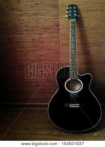 черная шестиструнная акустическая гитара в интерьере комнаты