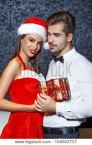 Man in tux get christmas present from santa girlfriend