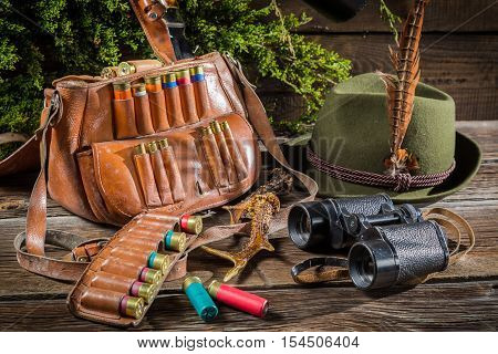 Bag with bullets binoculars and hat in a hunting lodge