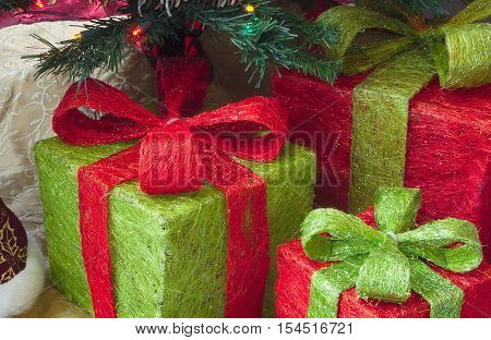 gifts with ribbons under decorated christmas tree