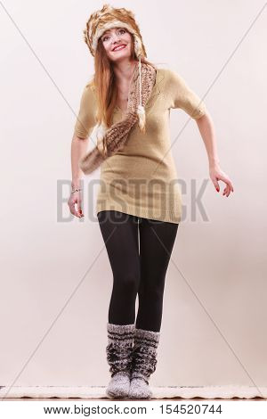 Winter fashion. Happy young woman in full length wearing fashionable wintertime clothes fur cap woolen warm socks posing