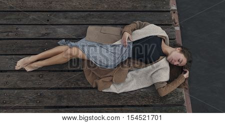 Beautiful sad girl lying on the wooden berth with her eyes close in warm clothes. Melancholy