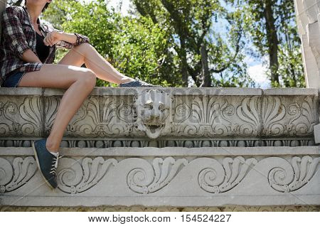 Anonymous woman sitting on the antient porch