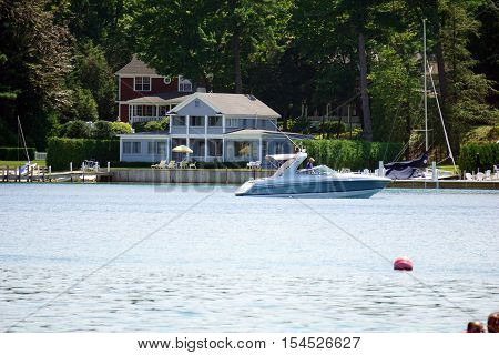 HARBOR POINT, MICHIGAN / UNITED STATES - AUGUST 1, 2016: A boat passes in front of lakefront homes in Harbor Point.