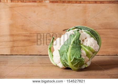 Fresh ripe cauliflower isolated on wood background. Food background