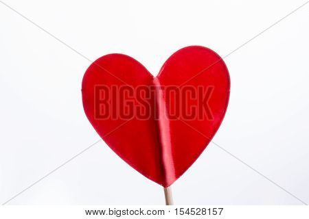 Little red color heart shape at the top of a stick
