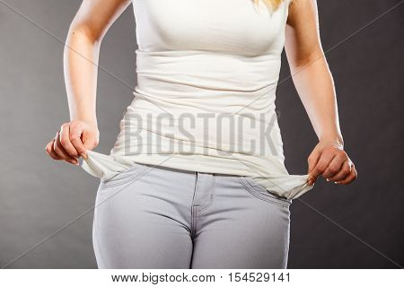 Financial difficulties bad economy no money concept. Young woman student girl showing empty pockets part of body female hips wearing pants
