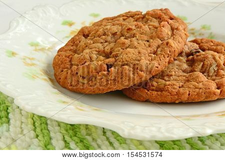 Fresh baked oatmeal raisin walnut cookies on pretty vintage plate in horizontal format. Macro with selective focus. Shot in natural light.