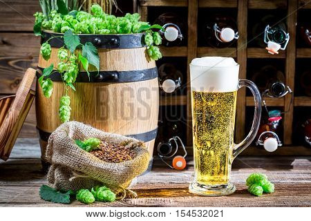Light beer made of fresh hops on old wooden table