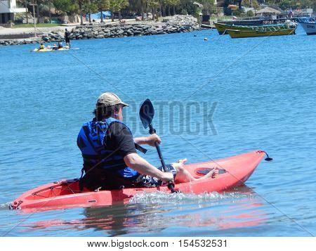 A man just doing kayaking at sea.