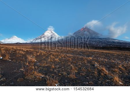 Volcanic landscape of Kamchatka Peninsula: view of eruption Klyuchevskoy Volcano lava flows on of volcano; plume of gas steam ash from crater. Russian Far East Klyuchevskaya Group of Volcanoes.