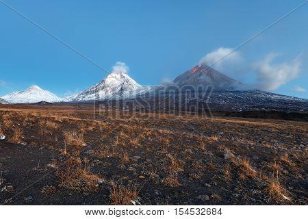 Volcanic landscape of Kamchatka Peninsula: view of eruption Klyuchevskoy Volcano lava flows on of volcano; plume of gas steam ash from crater. Russian Far East Klyuchevskaya Group of Volcanoes.