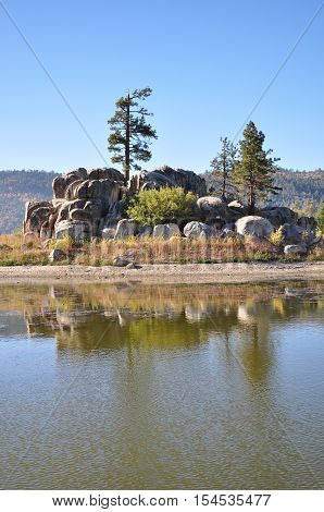 A ponderosa pine tree stands on top of a rocky island in Big Bear Lake in Southern California.