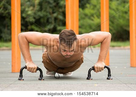 Push-ups - man fitness model training pushups outdoors. Fit male fitness trainer working out exercising in summer