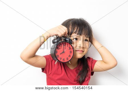 Lazy Asian girl holding alarm clock do not want to wake up. Little girl asking for more time to sleep. Alarm clock woke an upset girl. Sleepy girl is holding ringing alarm clock.