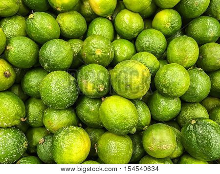 A large group of Thai green orange on sale in the market. This orange are grown in Thailand. Unlike most of imported orange, these Thai orange are much sweet and smaller.