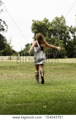 Young Caucasian Woman Running Away From Camera On Green Grass Wearing Dress And Sandals