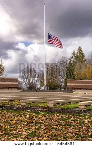 Old Glory waving in the wind at half mast in the Willamette national cemetery Oregon.