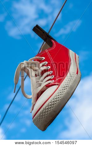 One red sneakers hanging on a clothesline against a blue sky closeup