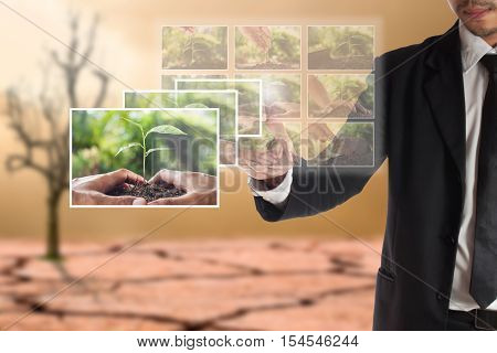 Business concept of CSR or Corporate Social Responsibility businessman select a photo on touch screen for plan csr