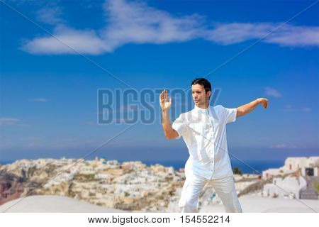 Handsome man practicing Tai Chi of the rooftops in Oia Santorini island Greece