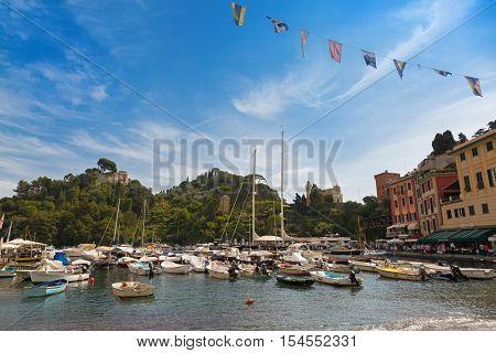 PORTOFINO, ITALY - SEPTEMBER 2016: Boats ships docking near restaurants, shops, colorful historical buildings at Portofino port, fishing village, Genoa province, Italy on September 23, 2016