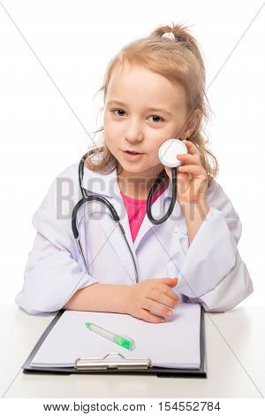 Girl 7 years with stethoscope in the doctor's suit playing photo on the white background