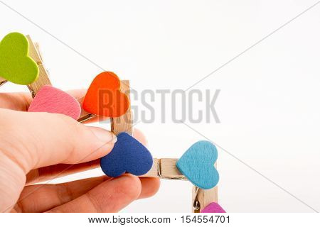 Colorful clothespin attached one another in hand form a zigzag
