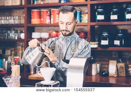 Portrait of professional bartender preparing alternative coffee in coffee machine