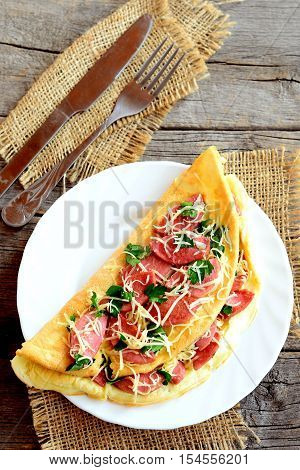 Egg omelette with grated cheese and fried sausages on a plate and on old wooden background. Fork, knife, burlap. Hearty omelette recipe. Top view