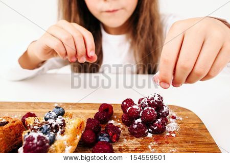 Unrecognizable girl decorating pastry close-up. Lassie cooking cakes with fresh berries at home. Homemade bakery, children culinary, pastry making concept