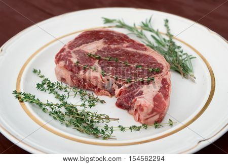 Rib eye steak in a rustic plate on wooden table