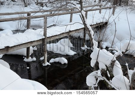 Fairy winter landscape with a brige over stream