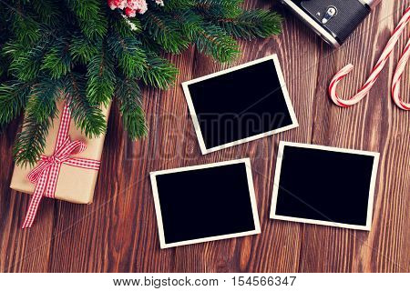 Blank photo frames with christmas gift box, pine tree and camera on wooden table. Top view. Toned