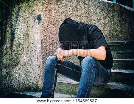 Toned Photo of Sad Teenager sit on the Street