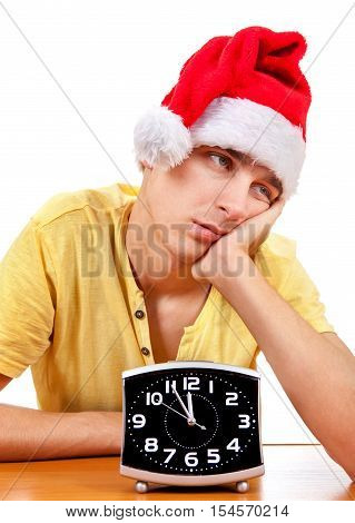 Bored Young Man in Santa's Hat with the Clock at the Table On The White Background