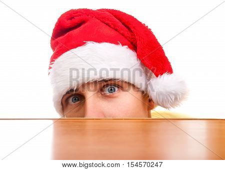 Frightful Young Man in Santa's Hat behind the Table on the White Background